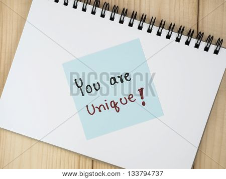 Handwriting word You Are Unique on color note paper and notebook with wood background leadership business concept