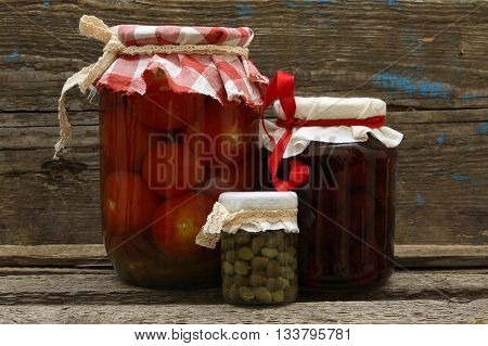 Preserve. Jar with strawberry jam pickled tomatoes and capers on wooden background