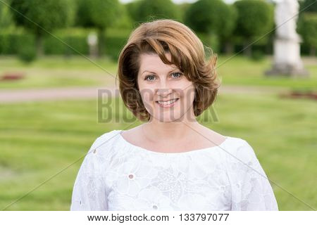 Portrait of a positive woman in a white blouse