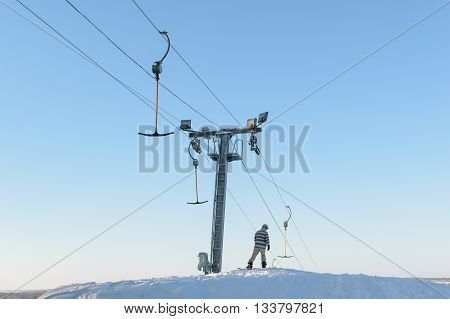 Snowboarder (skier) stands near the lift on top of a hill covered with snow and preparing to downhill