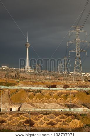 Milad Tower and power transmission lines above hillside against gray overcast sky of Tehran in autumn.