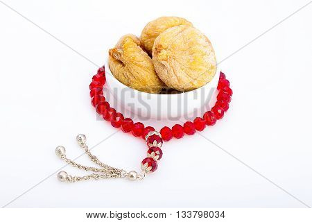 Tasty dried figs in a white plate with a red rosayr around for breakfast in Ramadan