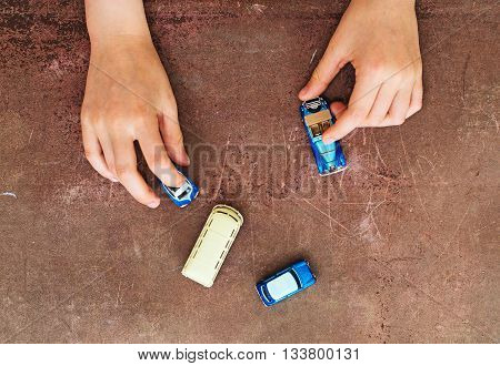 Child hands playing with miniature model cars.