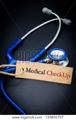 Medical check up word in paper tag with stethoscope on black background - health concept. Medical conceptual