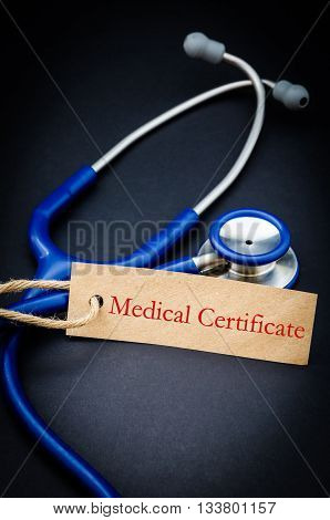 Medical certificate word in paper tag with stethoscope on black background - health concept. Medical conceptual