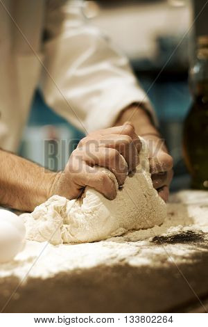 Male chef's hands kneading pizza dough on kitchen counter top