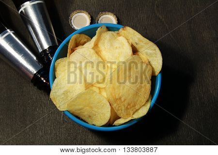 Two Beer Bottles, Bowl Of Chips, Wood Surface. Horizontal Format. The Bottle Is Without Label.