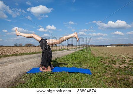 on an sunny day this man enjoys Mukta Hasta Sirsasana yoga in nature