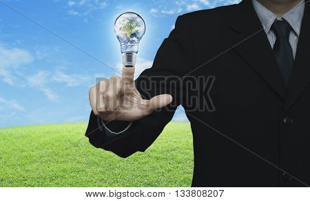 Businessman pressing earth globe in light bulb over green grass field with blue sky Energy conservation and environmental concept Elements of this image furnished by NASA
