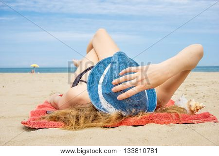 young woman relaxing lying down on sunny beach on a summer day