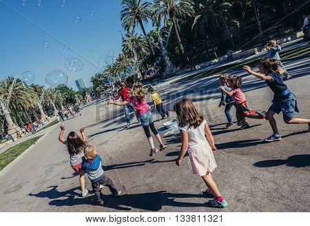 Barcelona Spain - May 22 2015. Children chases bubbles on Passeig de Lluis Companys in Barcelona