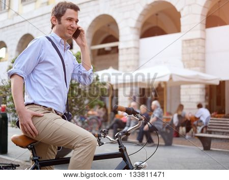Picture of a young business man who stopped on his bike to call someone on his smartphone