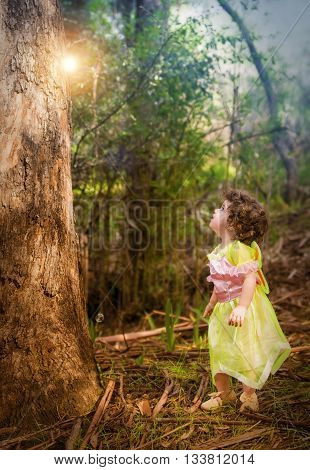 little girl in forest dressed as a fairy looking at a light