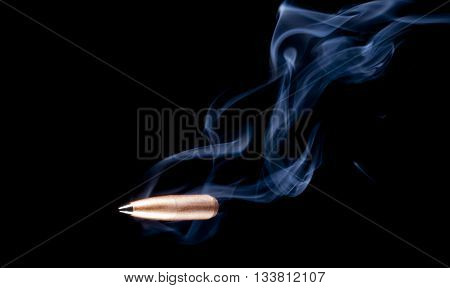 Smoke rising from a copper plated bullet with a black polymer tip