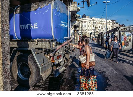 Belgrade Serbia - August 29 2015. Woman pours water from a water tanker in Belgrade