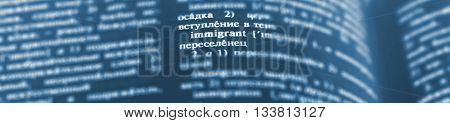Immigrant Definition Word Text in Dictionary Page. Shallow depth of field. Russian language translate . Blue and white image