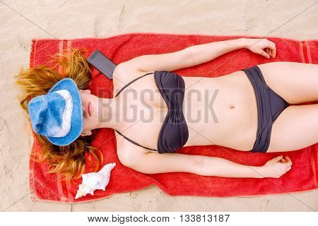 pretty woman in bikini sunbathing and sleeping on beach towel with a seashell and mobile phone and her face covered with hat seen from top