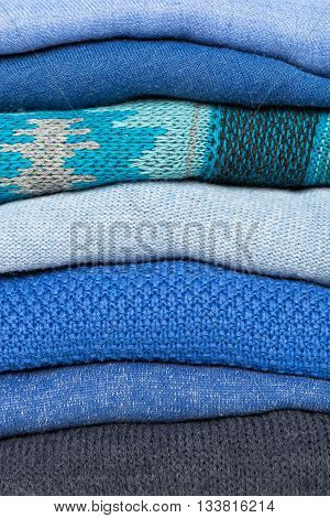stack of blue woolen knitted sweaters full frame