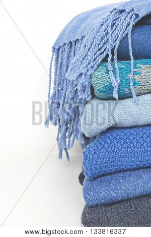 stack of blue woolen knitted sweaters and shawl with a fringe