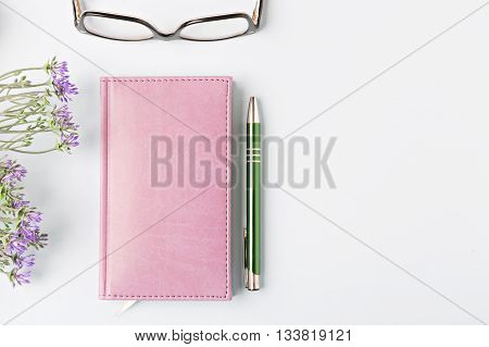 closed notebook with pen on blue table flat lay