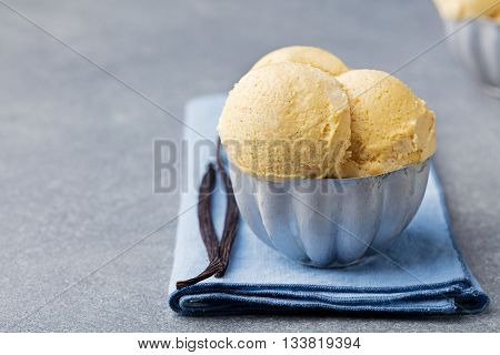 Vanilla Ice Cream with vanilla pods in metal vintage bowl. Homemade Organic product Grey background Copy space