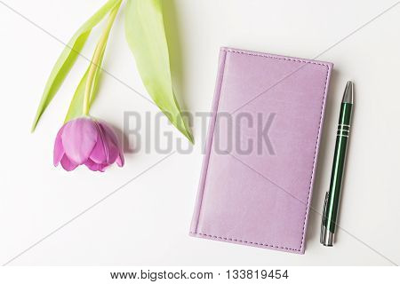 closed notebook with pen and flower flat lay