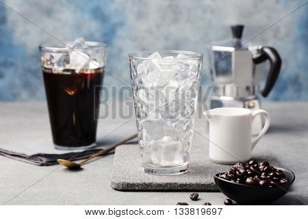 Ice coffee in a tall glass and coffee beans on a grey stone background.