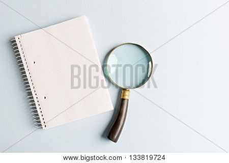 magnifier and notebook on blue background flat lay
