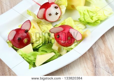 Mouse from radish. Mice made from radish. Radish for children. Raw radish. Children party. Radish mouse on fresh lettuce with cheese.