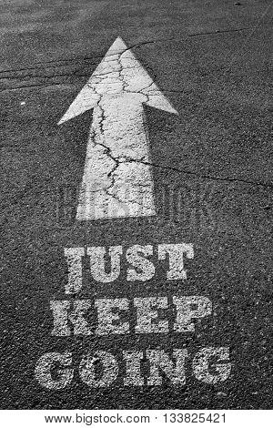 Arrow sign on asphalt surface with keep going word