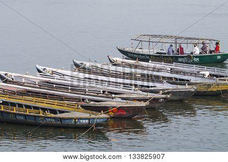 Varanasi, India - January 26, 2012:old Boats On Brown Waters Of Ganges River, Varanasi, India