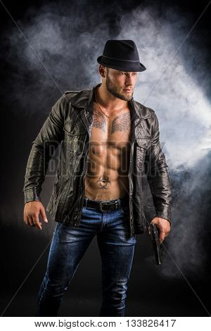 Handsome man wearing leather jacket on naked muscular torso, holding hand gun, on dark smoky background, looking to a side. Wearing fedora hat