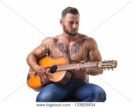 Portrait of muscular man with tattoo playing guitar.Isolated