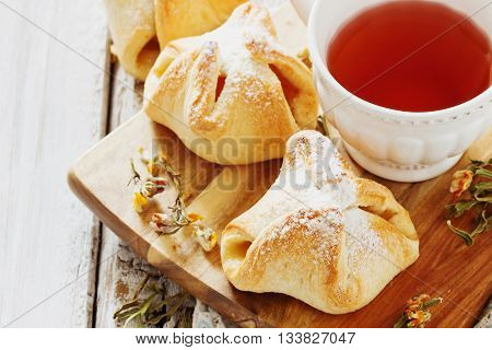 Freshly baked homemade scones and flower tea on the table. Homemade pastries . Close-up. Top view . Selective focus