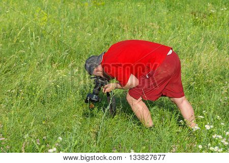 Hard bend - mature photographer taking a photo of wild nature