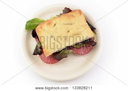focaccia salami and salad on dish on white background