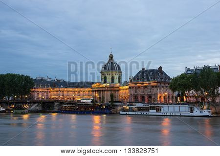 PARIS FRANCE - MAY 07 2015: The French Institute and Pont des Arts across the Seine river at night Paris France. The Institut de France ( French Institute) is a French learned society grouping five academies the most famous of which is the Academie frança