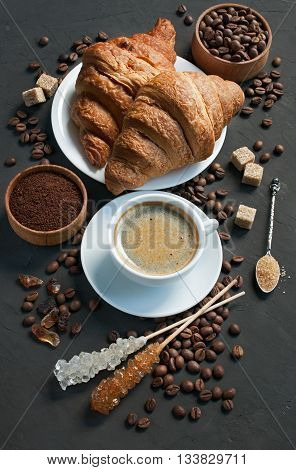 Breakfast with fresh croissants and coffee on a dark background