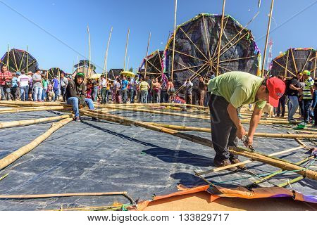 Sumpango Guatemala - November 1 2015: Man finishes preparing kite before raising it from ground at giant kite festival on All Saints' Day honoring spirits of dead.