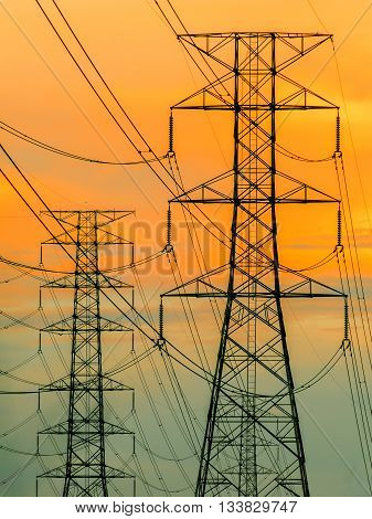 high voltage transmission line on the metal tower on sunset sky background