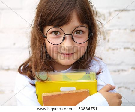 Little girl with glasses holding a books in their hands