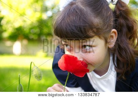 Little Girl Smelling A Red Poppy