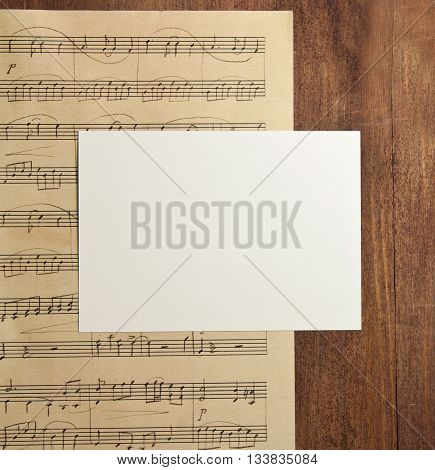 A photo of a blank white post card with copyspace on a piece of aged sheet music (piano concert) on a dark wooden background texture shot from above; an invitation template