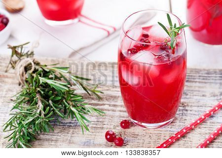 Cranberry and rosemary lemonade cocktail fizz on a wooden background.