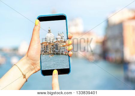 Female hands photographing with smart phone beautiful Grand canal with Santa Maria della Salute basilica in Venice.