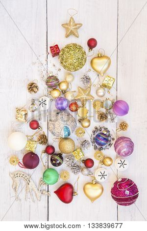 Christmas tree made of Christmas ornaments on white wooden background
