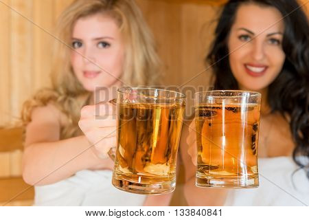 Glasses Of Beer In The Hands Of Women Who Are In The Finnish Sauna