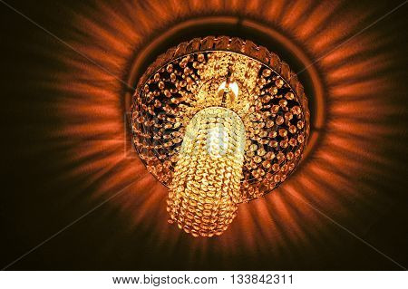 Switched on glass chandelier hanging from ceiling