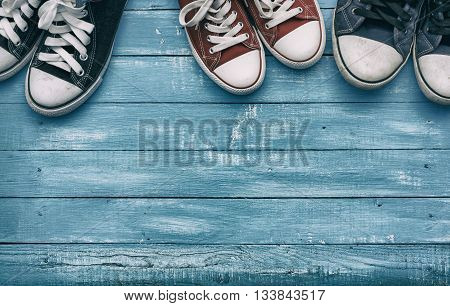 two pairs of men's sneakers and one pair of women's shoe on vintage background toning