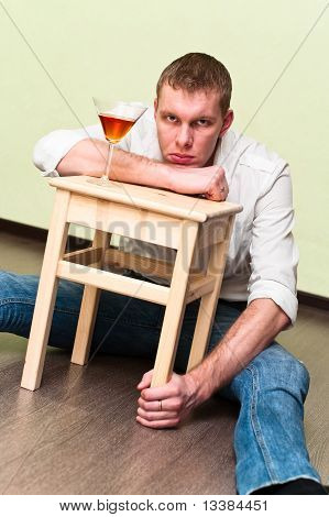 Drunken Man Sitting On Floor With Glass Of Alcohol